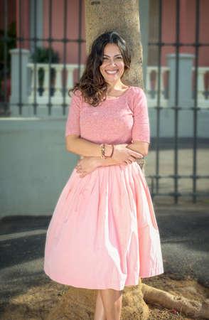Sonrisa de la señora en vestido rosa se inclina en un árbol Foto de archivo