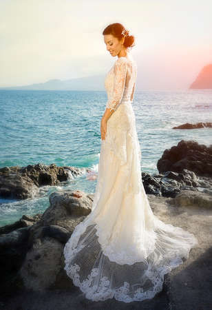 gown: wedding bride - standing on the ocean in the sunset Stock Photo