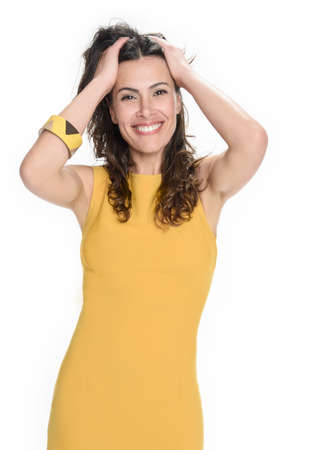 yellow dress: pretty woman in a yellow dress is standing in the studio and is posing
