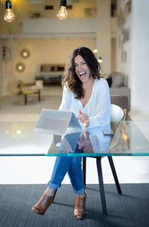 laughing out loud: La mujer est� sentada en la oficina con una libreta y se r�e a carcajadas