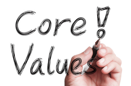 Hand with pen is writing Core Values on transparent white board.