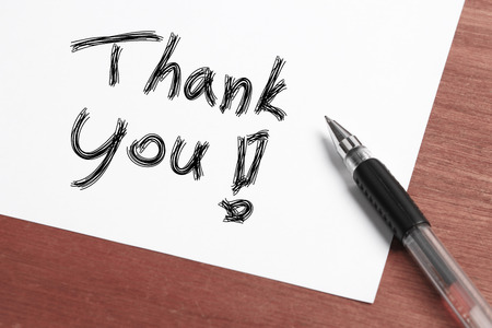 thank you note: Thank you Concept written on white paper with black pen aside. Stock Photo