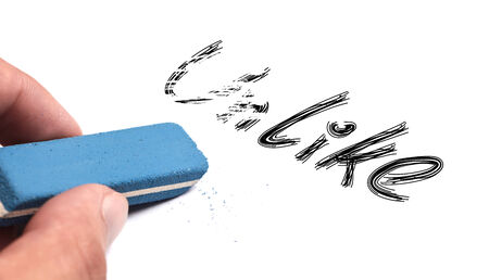 unlike: Unlike text is erased by a blue eraser which is held by hand. Stock Photo