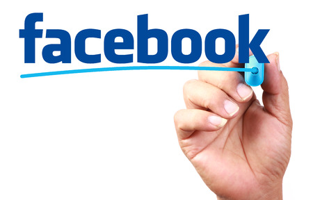 青色の透明ホワイト ボードに Facebook の書き込みと手。