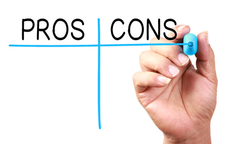cons: Hand with blue marker drawing Pros and Cons on transparent white board. Stock Photo