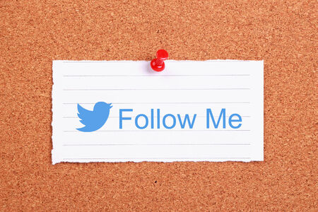 Twitter follow me note paper pinned on corkboard.