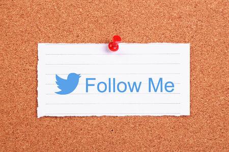 Twitter follow me note paper pinned on corkboard.