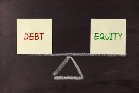 Debt and Equity Balance concept on blackboard. 写真素材