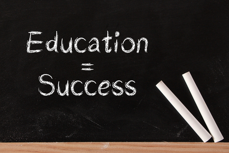 white chalks: La educaci�n es el concepto de �xito en la pizarra con dos tizas de color blanco.