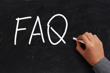 FAQ written on black chalkboard with white chalk in hand. photo