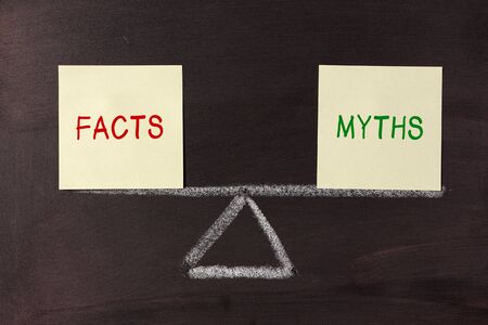 outweighing: Facts and Myths Balance concept on blackboard. Stock Photo