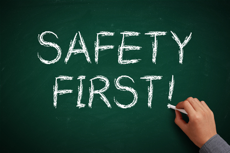 cautionary: Hand with white chalk writing Safety First on chalkboard. Stock Photo