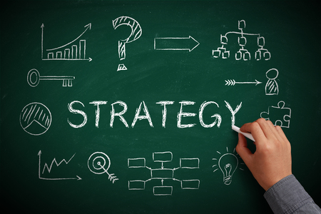 success strategy: Hand with white chalk drawing strategy concept on chalkboard. Stock Photo
