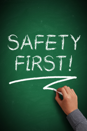 safety first: Hand with white chalk writing Safety First! on chalkboard. Stock Photo