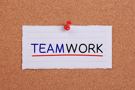 Teamwork text with line written on note paper pinned on corkboard. photo