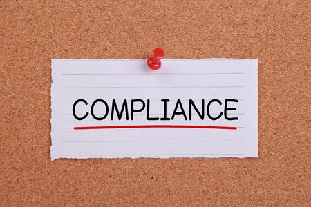Compliance concept note paper pinned on corkboard. Stock Photo