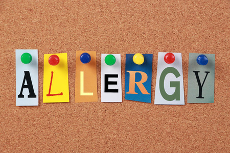 The word Allergy in cut out magazine letters pinned to a corkboard. photo