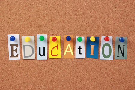 pin board: The word Education in cut out magazine letters pinned to a corkboard.