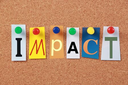 corkboard: The word Impact in cut out magazine letters pinned to a corkboard. Stock Photo