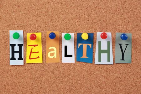 corkboard: The word Healthy in cut out magazine letters pinned to a corkboard. Stock Photo