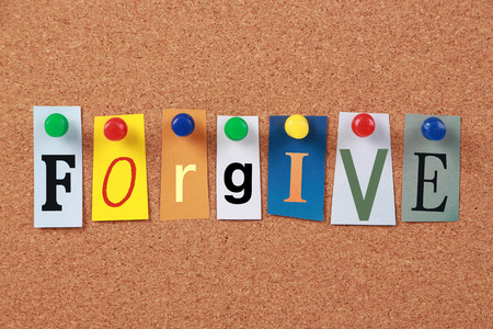 forgiven: The word Forgive in cut out magazine letters pinned to a corkboard. Stock Photo