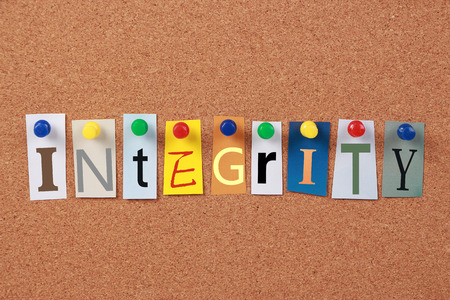 reputable: The word Integrity in cut out magazine letters pinned to a corkboard. Stock Photo