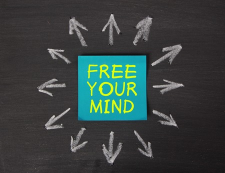 free your mind: Free Your Mind - relaxation or meditation concept - sticky note pasted on a blackboard background with a lot chalk arrows.