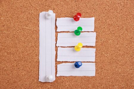 urgent announcement: Some pieces of blank note papper are pinned to a corkboard.