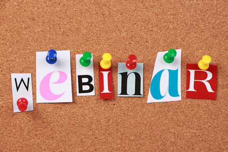 distance learning: The word Webinar in cut out magazine letters pinned to a corkboard. Stock Photo
