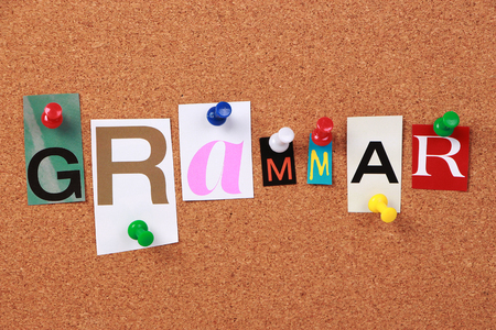 The word Grammar in cut out magazine letters pinned to a corkboard.