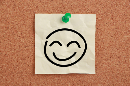 straight pin: Smile face sticky note pinned on corkboard.