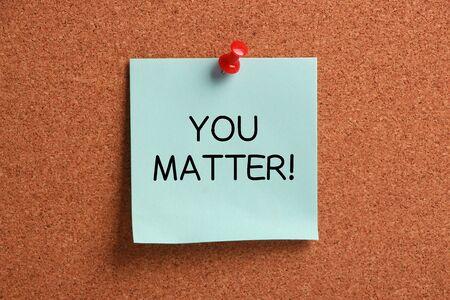 business matter: You Matter sticky note pinned on cork.