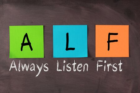 listen fist: Always listen first(ALF) concept with colorful notes and white chalk words on blackboard. Stock Photo