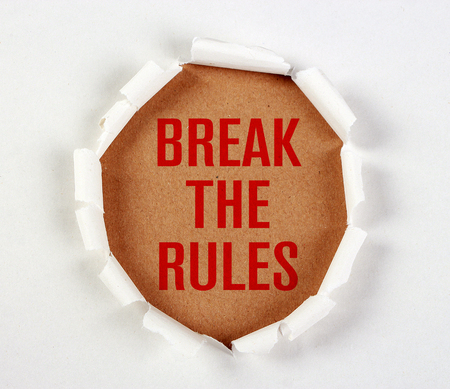 short phrase: Break the rules with tear paper on brown. Stock Photo