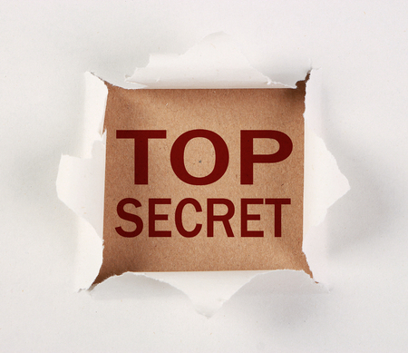 tear paper: Top secret with tear paper on brown. Stock Photo