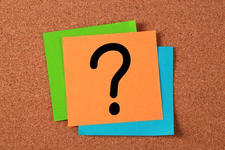 Question mark note pasted on cork board. photo