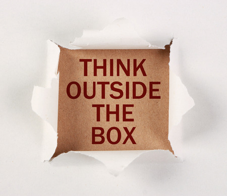 tear paper: Think outside the box with tear paper on brown. Stock Photo