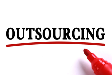 underline: Outsourcing text is on white paper with red underline which is written by the red marker. Stock Photo
