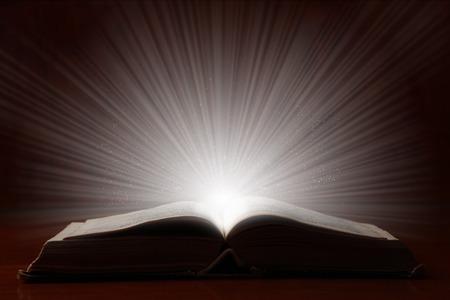 テーブルの上の明るい魔法光と古い本。