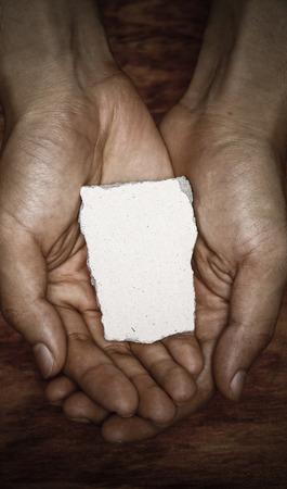 arrepentimiento: Bloque de piedra en blanco en la mano con fondo oscuro. Foto de archivo