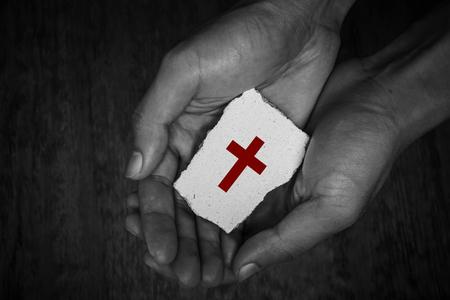 devout: Cross stone block in hands with dark background.