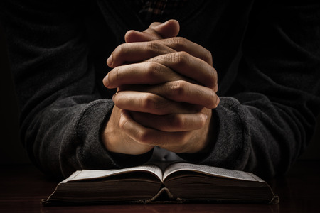 Praying man hand and bible on desk.