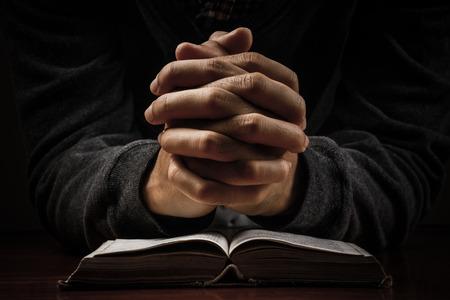 Biddende mens hand en bijbel op het bureau.