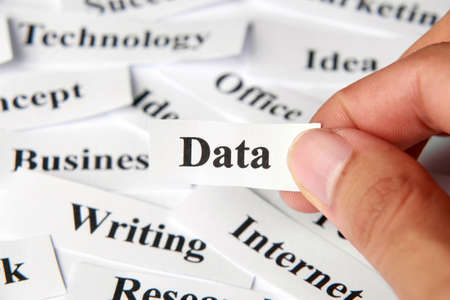 forewarning: Data word paper in hand with the background of other words. Stock Photo