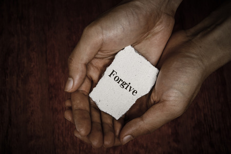 worship hands: Forgive stone block in hands with dark background. Stock Photo