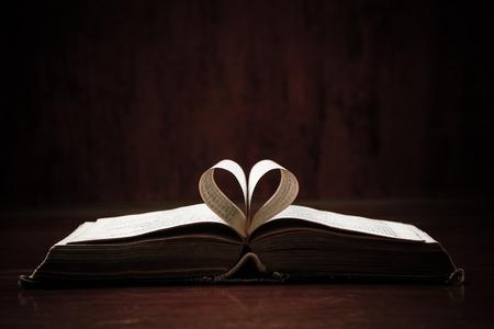 leer biblia: Abrir Santa Biblia en una mesa. Ideal para un mensaje de texto.