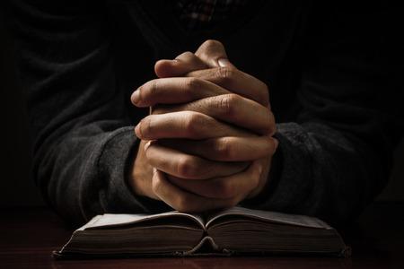 cristianismo: Manos de un hombre orando en soledad con su Biblia.