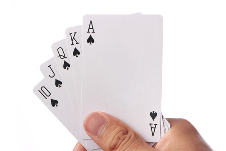 hand holding house: Hand holding royal straight flush playing cards poker. Stock Photo