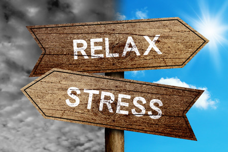 destress: Relax Or Stress concept road sign with cloudy and sunny sky background. Stock Photo