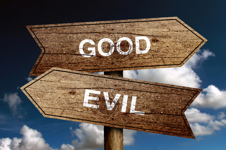 good and bad: Good Or Evil concept road sign with blue sky background. Stock Photo